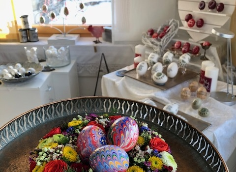 Bunt marmorierte Enteneier liegen in einem bunten Frühlingsblumenkranz. Im Hintergrund ist ein österlich, frühlingshaft dekorierter Verkaufsraum mit vielen Ostereiern zu sehen.