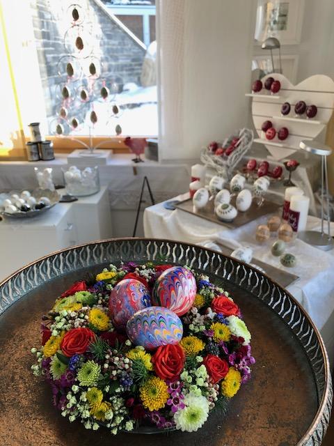 Bunte Frühlingsgrüße mit marmorierte Enten-Eiern in leuchtenden Farben. Sie liegen in einem frischen Blumenkranz. Im Hintergrund eist ein frühlingshaft dekorierter Raum.