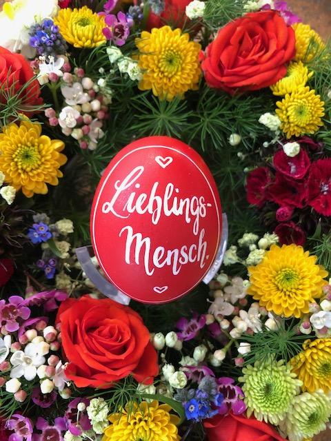 """Rot grundiertes Hühnerei mit weißer Handlettering-Gestaltung """"Lieblingsmensch"""". Das Ei liegt in einem farbenfrohen Blumenkranz. Ein bunter Frühlingsgruß"""